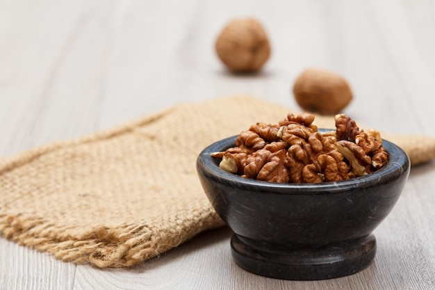 나무 배경에 자루가 있는 돌 그릇에 껍질을 벗긴 호두. 유용한 영양가 있는 단백질 제품. 필드의 얕은 깊이.