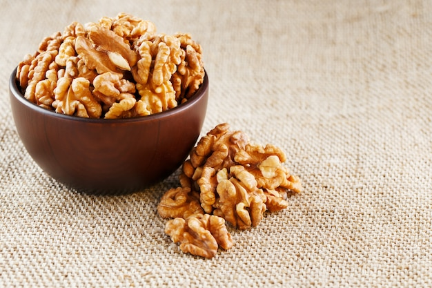 Peeled walnuts in a wooden, dark brown cup on a burlap cloth