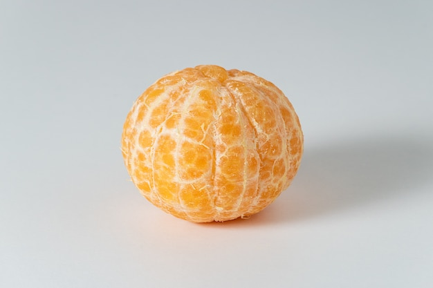 Очищенные целые плоды мандарина или мандарина на белой поверхности