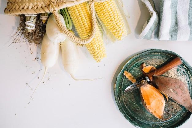 Peeled yam near corn and radish