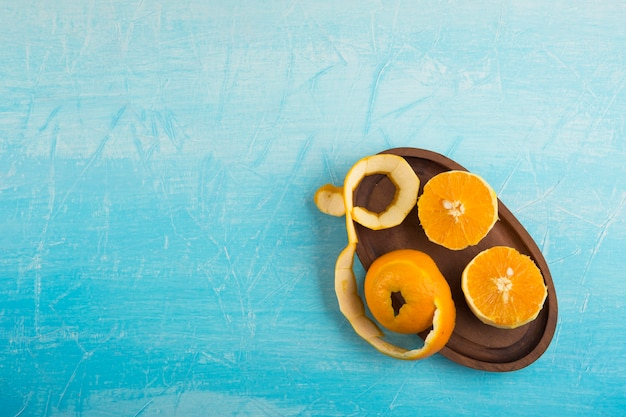 Очищенные желтые апельсины на деревянном блюде, внизу