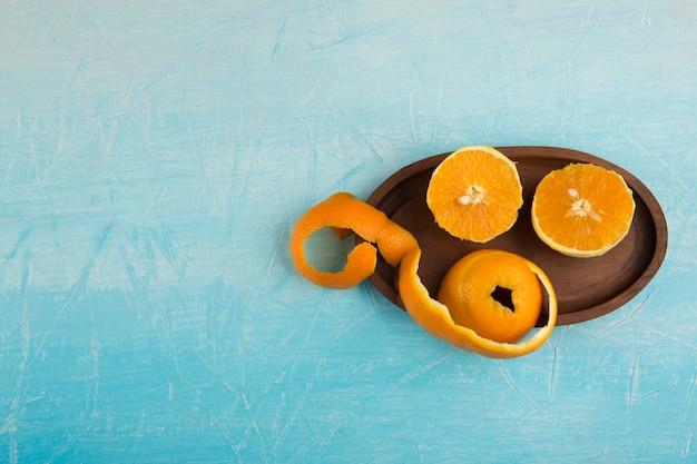 Очищенные желтые апельсины на деревянном блюде