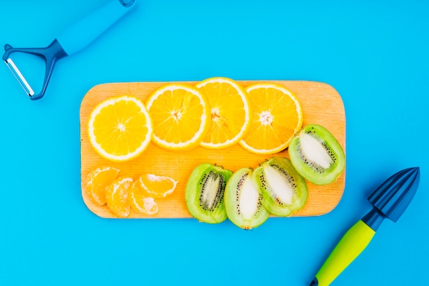 Peeler and hand juicer with oranges and kiwi slices on chopping board against blue backdrop