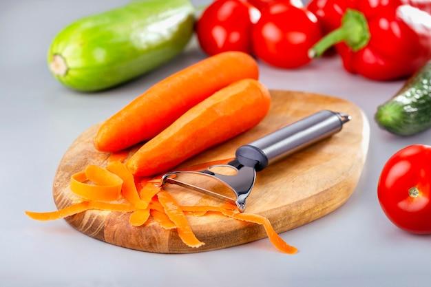자르고 보드에 샐러드 당근 껍질. 건강한 식사 요리. 식탁에 신선한 유기농 야채입니다.