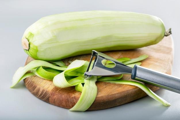 필러로 신선한 녹색 호박 껍질. 야채 필러로 생 스쿼시를 청소하는 과정.