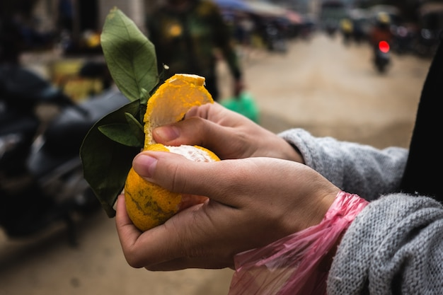 Peeling fresh tangerine at street market