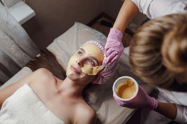 아름다운 얼굴 피부를위한 필링 골드 마스크. 환자를위한 미용 절차를하는 미용사