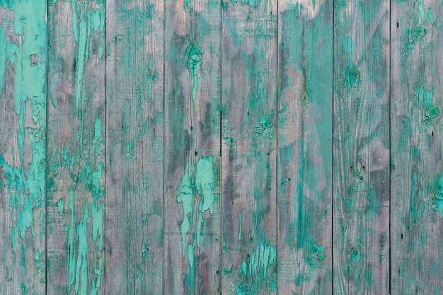 Peeling green paint on old rustic wooden panels, texture background