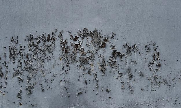 壁のシームレスなテクスチャに灰色のペンキをはがします。素朴な灰色のグランジ素材のパターン。