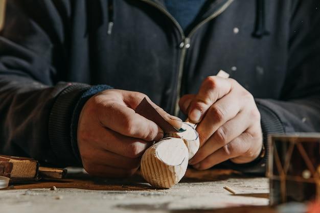 アトリエでミニ木製工芸品の皮をむく