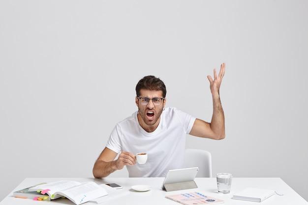 Обидчивый небритый дизайнер-мужчина сердито поднимает руку