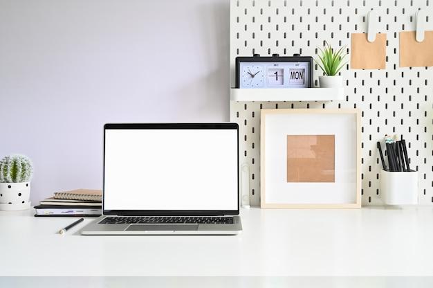 Ноутбук, pegboard и канцелярские принадлежности рабочей области на белом офисе стола.