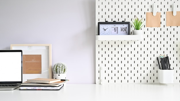 Копирование пространства макет ноутбука, pegboard, фоторамки и канцелярских принадлежностей на белом столе