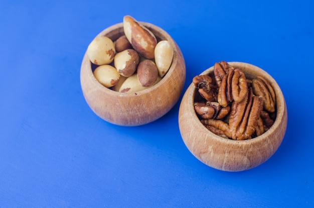 Pekan and brazil nuts on blue background. healthy food