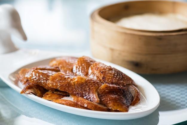 Кожа мяса утки по-пекински гриль с блинами листьев лотоса в корзине. знаменитая китайская традиционная еда.