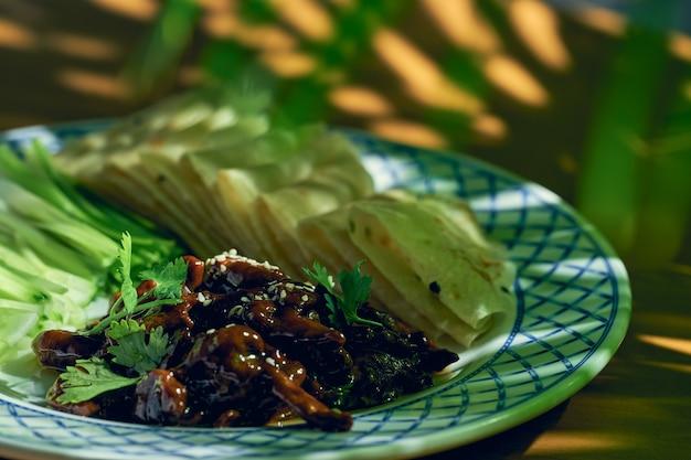 Свинина или утка по-пекински с салатом из огурцов и китайским хлебом на тарелке. китайская кухня