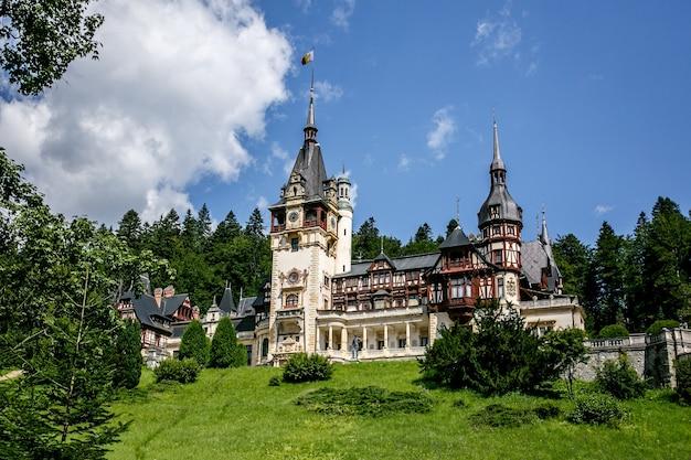 Замок пелеш в румынии, европе. голубое небо, зеленая трава, летнее время.