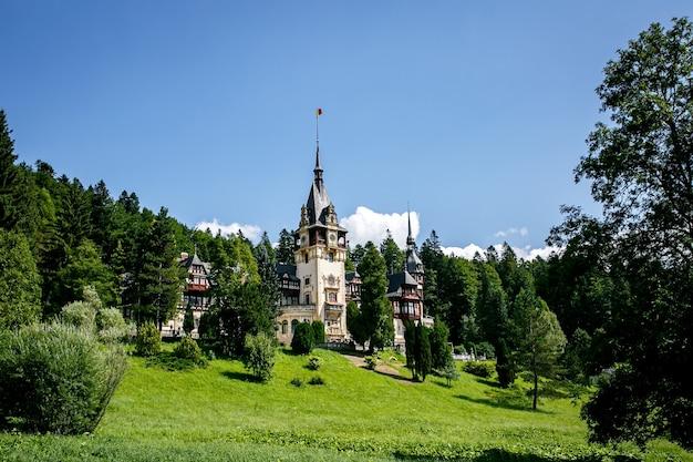 Peles castle in romania, europe. blue sky, green grass, summer time.