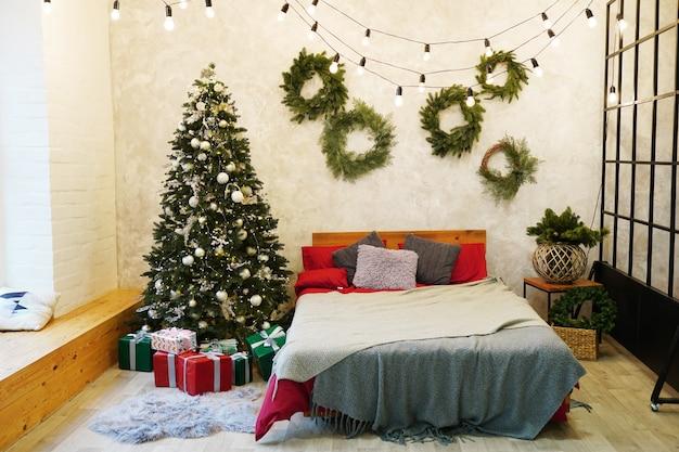 ペレットベッド、プレゼントやおもちゃのある木、クリスマスボール、大きな窓。