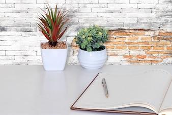 白いテーブルにペンと空の開いたノートブック