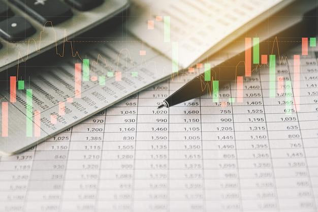 トレーディンググラフ付きの会計レポートのペンと電卓ビジネスと財務の概念