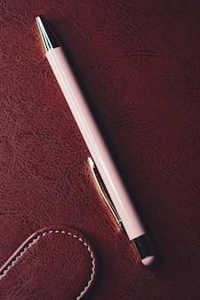 Ручка и кожаный портфель в офисе, крупным планом