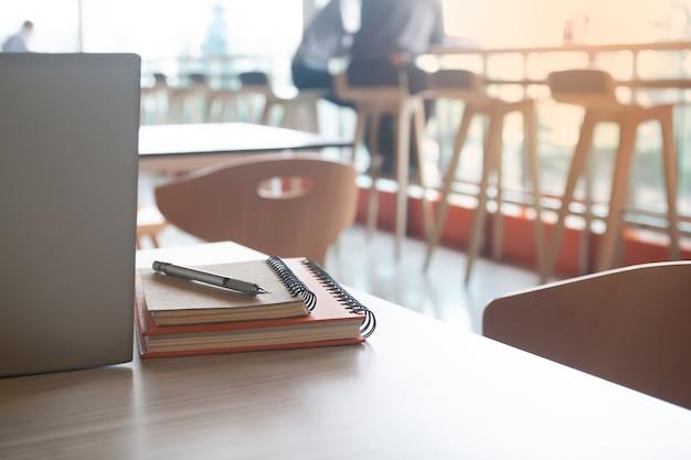 ペンとモダンなカフェのテーブルの上のラップトップコンピューターのノート。コワーキングスペース