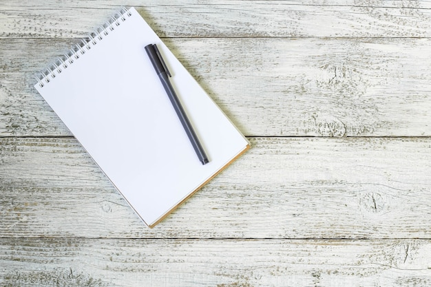白い木製のテーブルの上のペンとメモ帳。