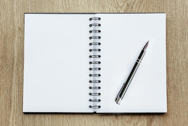 木製の机の上のペンとメモ帳。ビジネスコンセプト、白紙