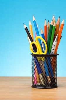 Ручка и ручки в держателе на синем фоне из дерева
