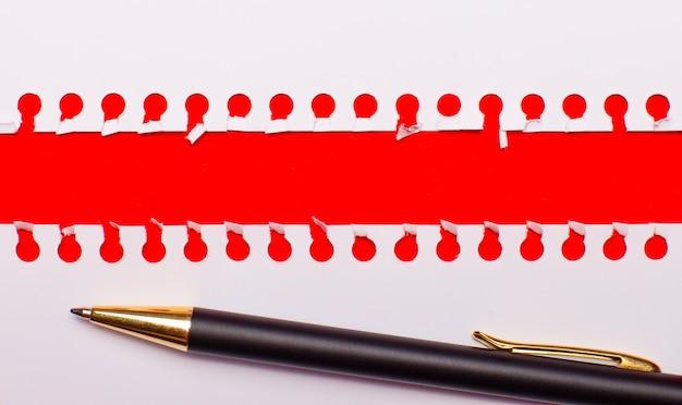 テキストやイラストのコピースペースと明るい赤の背景にペンと白の破れた紙のストリップ。レンプレート