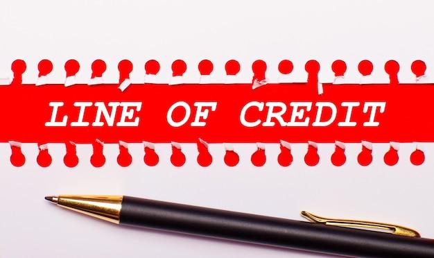 Ручка и белая рваная бумажная полоска на ярко-красном фоне с текстом линия кредита