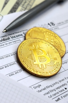 The pen, bitcoins and dollar bills is lies on the tax form 1040