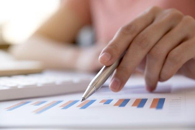 Ручка деловая женщина указывает и анализирует график с помощью калькулятора и ноутбука в домашнем офисе