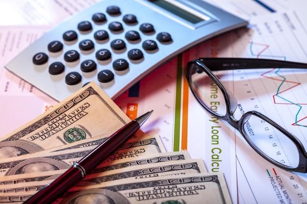 Ручка, калькулятор, очки и банкноты на бизнес-графиках и диаграммах