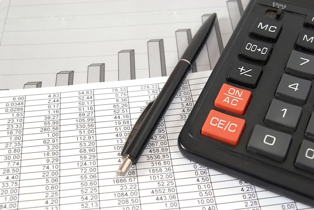 Pen and calculator on paper table with finance diagram