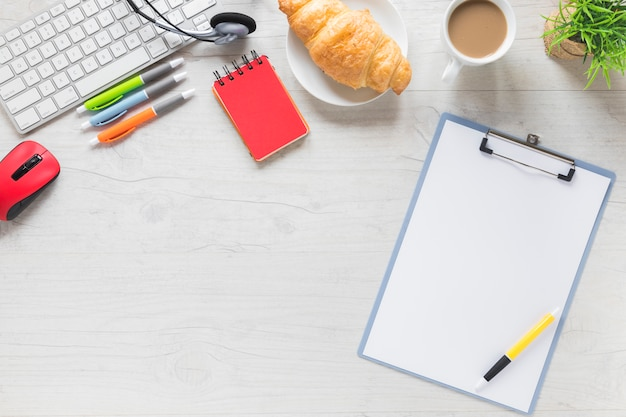 Pen on clipboard with breakfast and office stationeries on white table