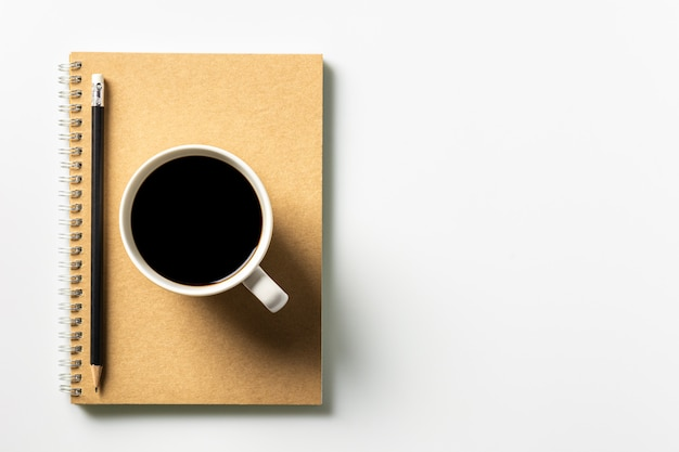 Pen and a coffee cup on diary book at desk. - work from home concept.