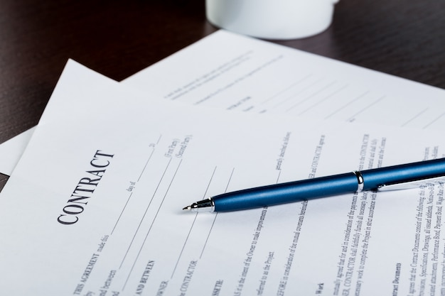 Pen and contract papers on wooden desk