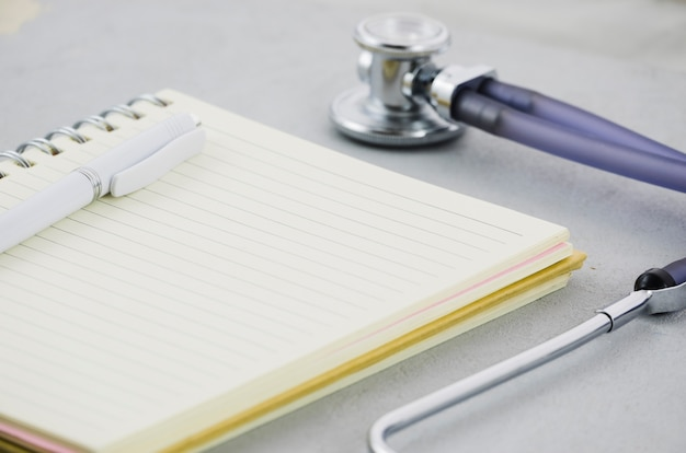 Pen on diary with stethoscope on grey backdrop