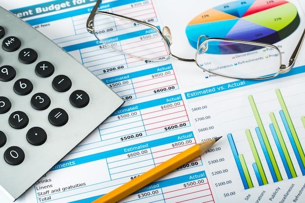 Ручка, очки и калькулятор на бизнес-графиках и диаграммах