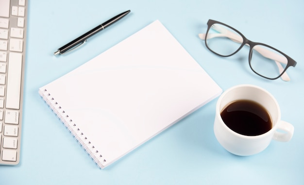 Pen; eyeglasses; coffee cup; keyboard and blank spiral notepad on blue background