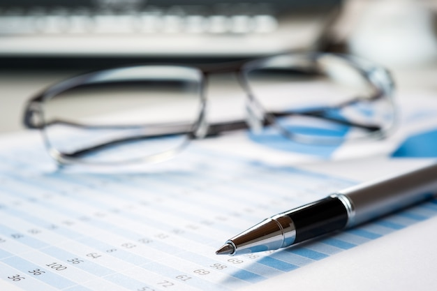 Pen and eyeglasses on financial documents, business and finance concept