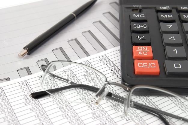財務図と紙のテーブル上のペン、メガネ、電卓