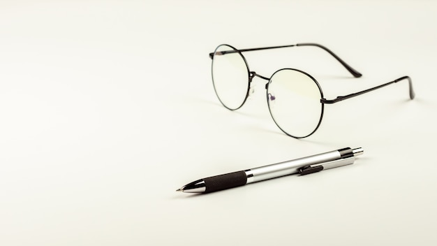 Pen and glasses on white desk background.