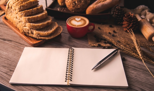 The pen is placed on a white notebook spread on a table with coffee and bread placed.