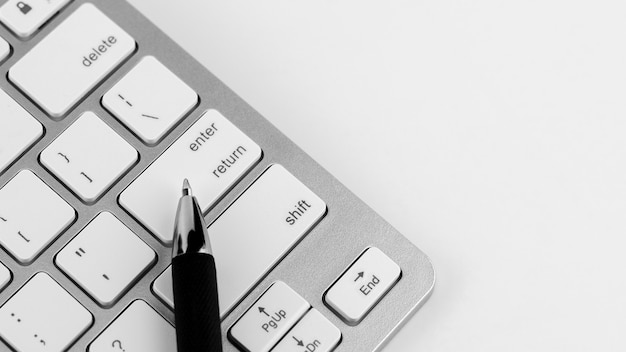 Pen and keyboard on white desk background.