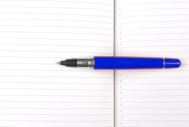 開いたノートに横たわっているペン。ビジネスと教育の科目