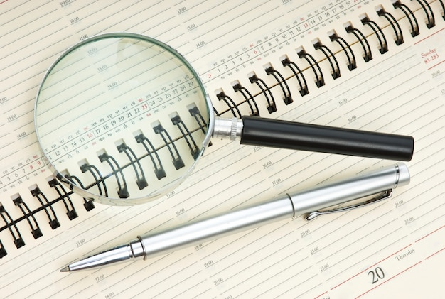 Pen and magnifying glass on the calendar