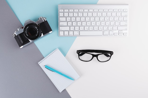Pen near notebook, camera, eyeglasses and keyboard
